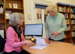 A visitor borrowing a book from Love Weston Library